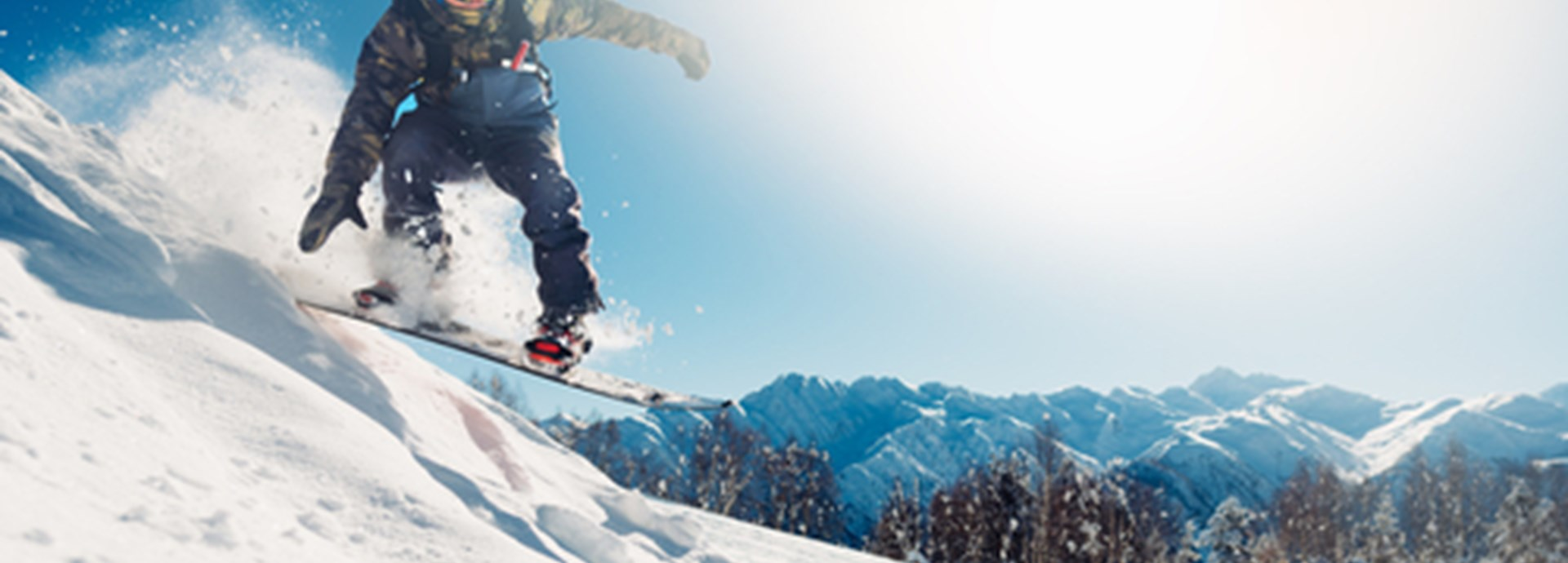 snowboarder is jumping with snowboard from snowhill on holidays